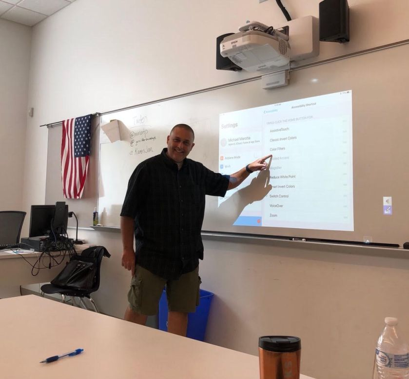 Mike pointing at projection on whiteboard showing iPad Accessibility features