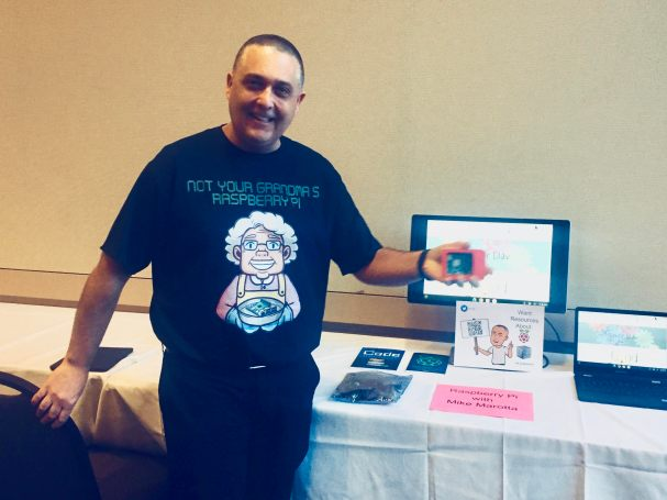"""Mike standing in front of table displaying Raspberry Pi computer and parts. Mike's shirt has a picture of a Grandma holding a pie pan and the caption says """"Not Your Grandma's Raspberry Pi"""""""